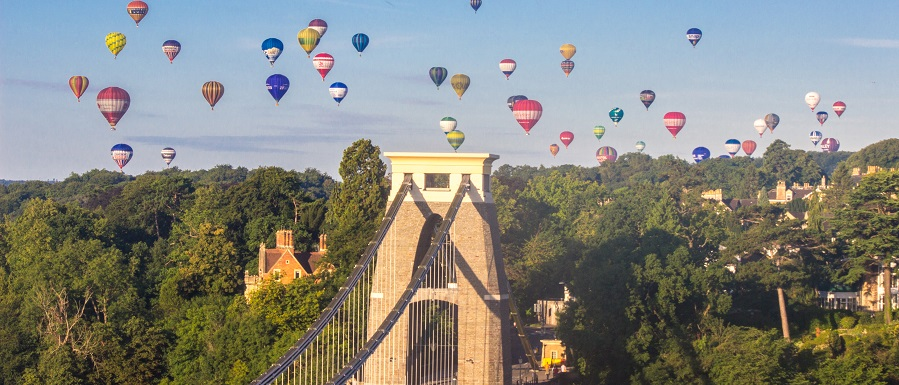 Clifton suspension bridge on a sunny afternoon with colourful hot air balloons in the sky above.