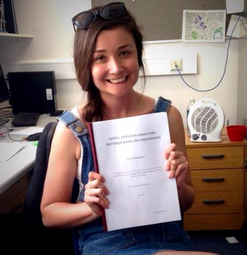Photo of Emily McNaughton smiling and holding her thesis