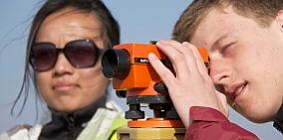 Two students using surveying equipment