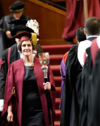 A female member of staff is dressed in a red gown and is holding a ceremonial staff featuring the University crest. She is leading a procession of staff members from the stage.