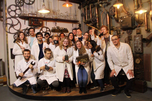 Neural Dynamics students wearing white coats and holding comical old fashioned items like an antique camera and a giant spanner.