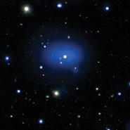 X-rays from Chandra are displayed as the diffuse blue region, while the individual galaxies in the cluster are seen in white, embedded in the X-ray emission