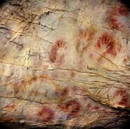 The 'Panel of Hands', El Castillo Cave showing red disks and hand stencils made by blowing or spitting paint onto the wall. A date from a disk shows the painting to be older than 40,800 years making it the oldest known cave art in Europe.