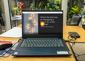 A mediasite video about redesigning a lecture for online teaching on a laptop. On the table the laptop is on, there is also a tablet, a mouse, a hard drive and sheets of paper. A garden is visible in the background.