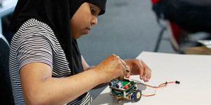 School girl building electronic vehicle