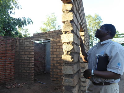 Malawian researcher inspects brick building