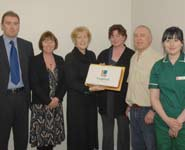 Lynne Hill, Chief Executive (3rd left), presenting an 'LVS' cake to members of staff on the first day of business